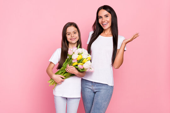 Photo portrait of little girl keeping tulips bunch with smiling mother on 8 march isolated pastel pink color background