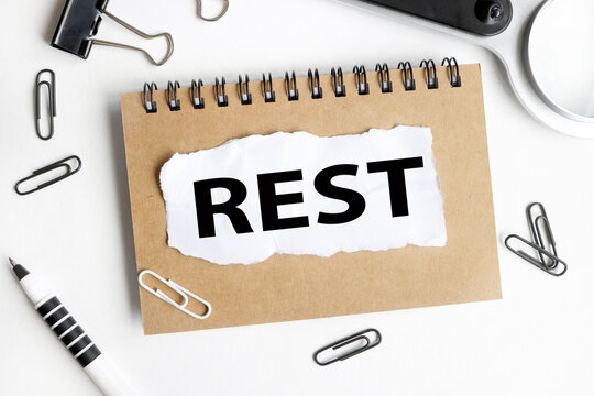 REST. Text on white notepad paper on light background