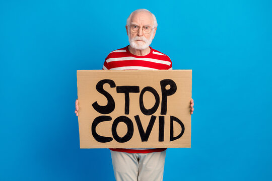 Portrait of attractive worried grey-haired man holding stop covid mers cov poster isolated over bright blue color background
