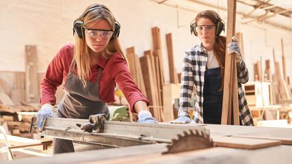 Fototapeta Women as carpenter apprentices at the circular saw obraz