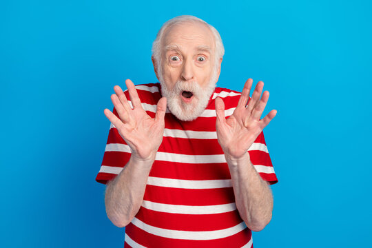 Photo of scared old grey hairdo man wear red t-shirt isolated on bright blue color background
