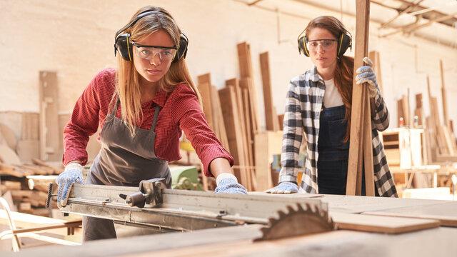Women as carpenter apprentices at the circular saw