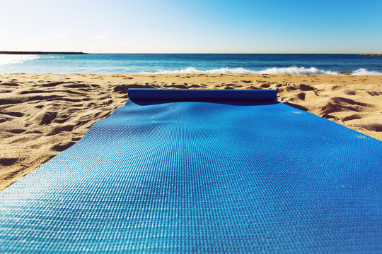 Blue yoga mat is on a sandy beach by the sea. Barcelona, Spain