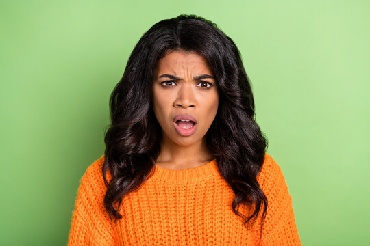 Photo of shocked impressed dark skin woman wear orange sweater open mouth isolated green color background
