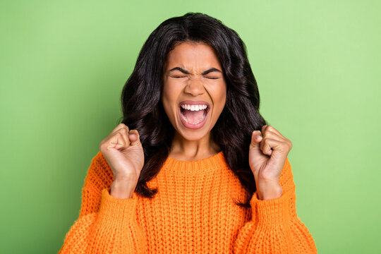 Photo of impressed funky dark skin woman wear orange sweater open mouth rising fists isolated green color background