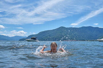 child swimming, splashing with water  and enjoing holidays at the Lake Maggiore (Lombardy) in Italy. Active girl on a sunny summer day at the lake. Wall mural