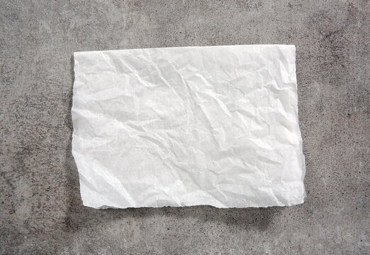 White paper napkin on grey stone table top view,food advertisement element,empty space blank.Baking paper.