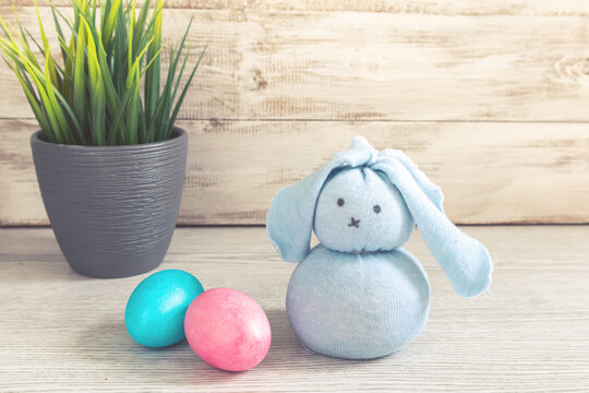 Toy Easter bunny and painted eggs on a wooden background.
