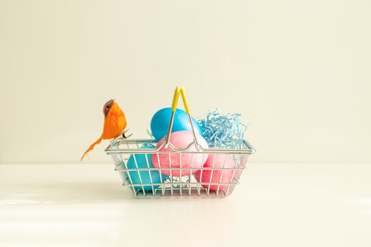 Shopping basket with colored eggs and orange bird.