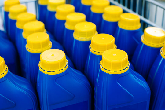Small plastic canisters with chemical liquid. Blue bottles with a yellow cap at an industrial plant. No marking. Close-up