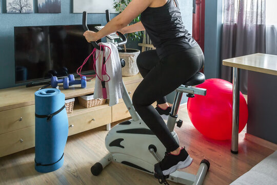 Wellness Fitness  home, distance learning with  virtual instructor. Woman sportswear sports  stationary bike home. Sports and leisure concept locked  fitness apps online, lockdown quarantine,stay fit