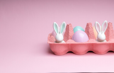 Easter colorful photografie with eggs group and bunny egg  on pink background, copy space