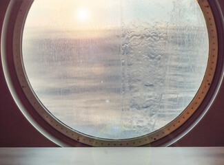 Round porthole of a sea cruise ship with water jets outside. Concept of sea travel