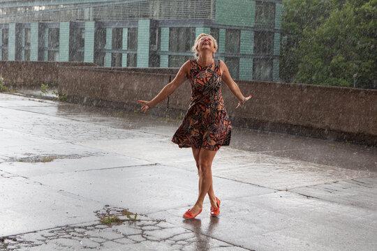 Attractive caucasian female dancing under the summer rain