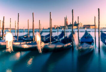 View on Venice and gondolas with purple sunset