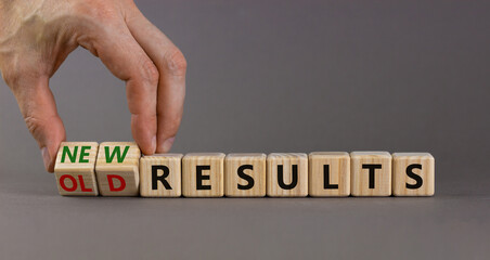 New vs old results symbol. Businessman turns the wooden cube and changes words 'old results' to 'new results'. Beautiful grey background. Business, new or old results concept. Copy space.