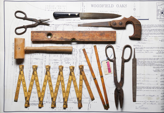 Variety of vintage hand tools on property map, overhead view