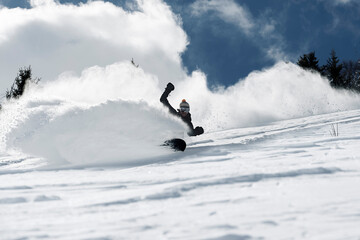 Male snowboarder speeding down mountainside, low angle view, Alpe-d'Huez, Rhone-Alpes, France