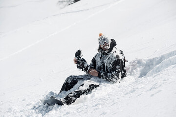 Male snowboarder covered in snow sitting on mountainside, Alpe-d'Huez, Rhone-Alpes, France