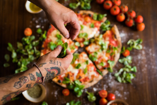 Chef garnishing pizza with basil leaves on kitchen worktop