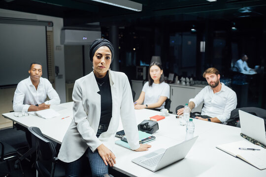 Young businesswoman in front of team at conference table meeting, portrait