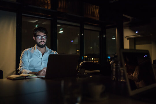 Mid adult businessman in office at night typing on laptop