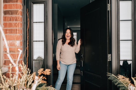 Mid adult woman opening house front door, portrait