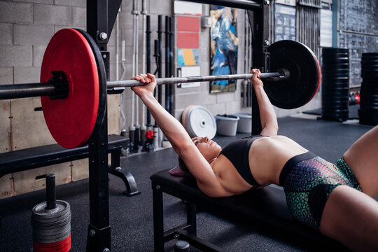 Young woman training, lying on weights bench in gym preparing to lift barbell