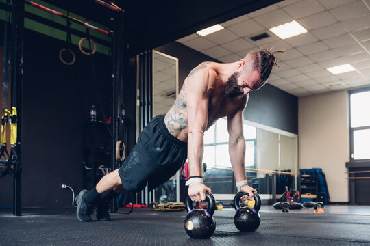 Young man training in gym, doing push ups from kettle bells