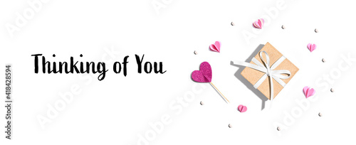 Thinking of you message with a small gift box and paper hearts