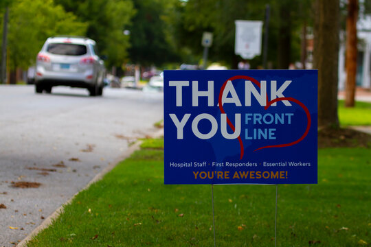 "close up image of a yard sign by the street that says ""Thank you' to all front line health care workers for their efforts during the COVID-19 pandemic."