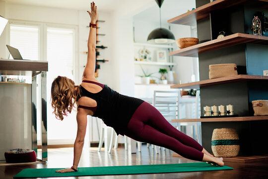 Middle aged yogi woman doing yoga at home