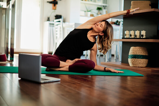 Woman practicing yoga at home with video tutorial.