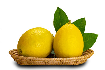 Fototapete - Lemons with leaves in a bamboo tray on white background with clipping path.