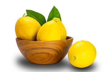Fototapete - Ripe lemons with leaves in a wooden bowl on white background with clipping path.