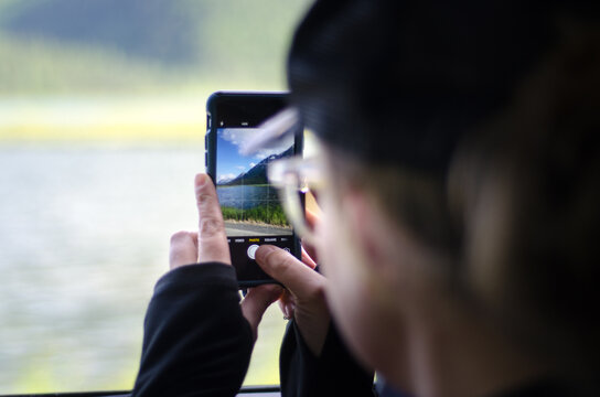 Woman taking photo of Alaska on iPhone