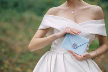 A bride in a white dress, with a beautiful manicure, holds an envelope in nature with a note from the groom. Wall mural
