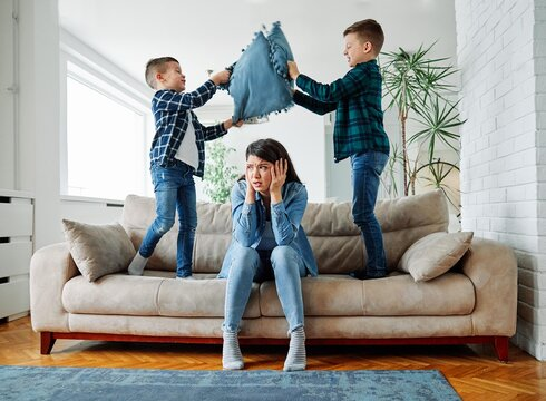 mother son family tired headache problem jumping hyperactive child boy kid sofa pillow