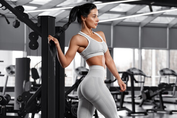 Athletic girl working out in gym. Fitness woman in leggings