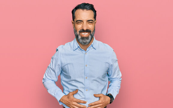 Middle aged man with beard wearing business shirt smiling and laughing hard out loud because funny crazy joke with hands on body.