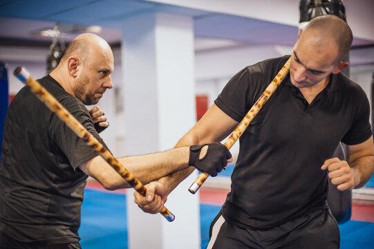 Instructor and student practice filipino escrima stick fighting technique