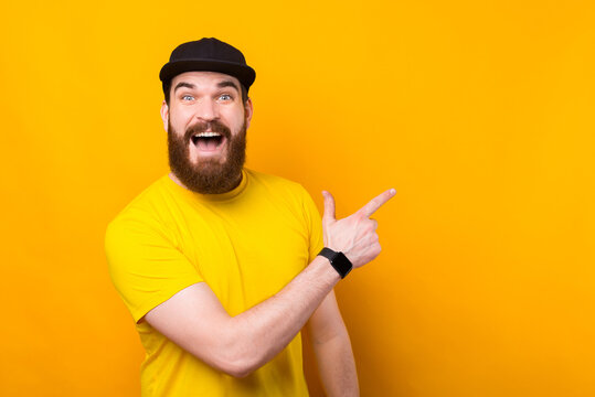 Cheerful happy bearded man in yellow tshirt pointing away and screaming
