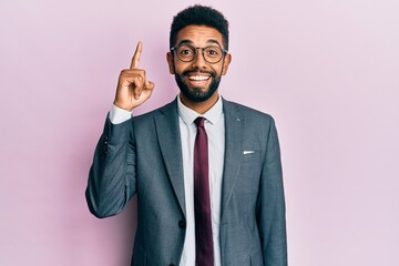 Handsome hispanic business man with beard wearing business suit and tie pointing finger up with successful idea. exited and happy. number one. Wall mural
