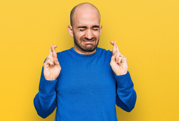 Fototapeta Young hispanic man wearing casual clothes gesturing finger crossed smiling with hope and eyes closed. luck and superstitious concept. obraz