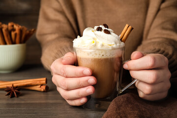 Woman holding cup of delicious coffee with whipped cream and cinnamon at wooden table, closeup