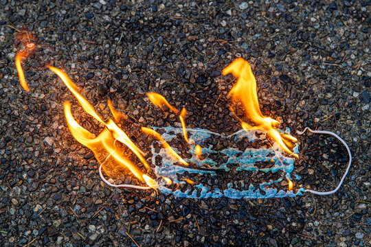 A medical face mask burns in flames as the coronavirus pandemic ends. The fire represents a protest of the mask mandate imposed by government officials during the Covid-19 virus outbreak.