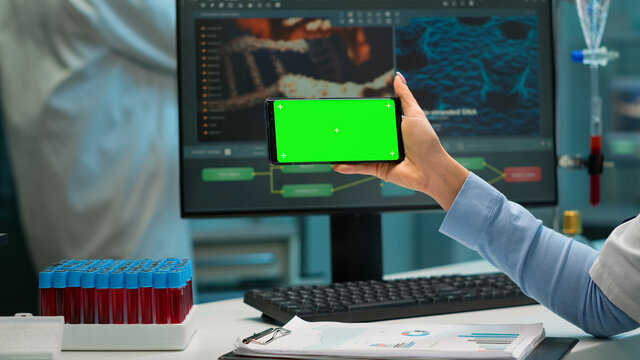 Close up of scientist woman holding smartphone with green mockup in modern equipped lab. Team of microbiologists doing vaccine research writing on device with chroma key, isolated display.
