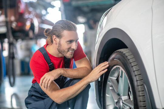 Man in overalls crouched near car wheel