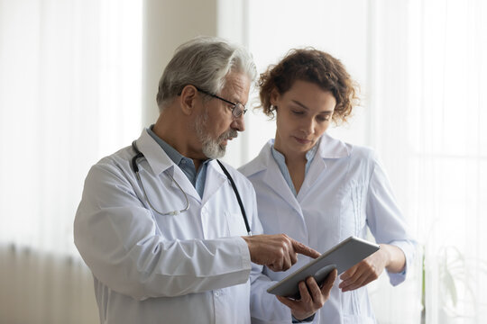 Focused mature male doctor and female nurse look at tablet screen discuss anamnesis together. Concentrated diverse medical professionals use pad device, engaged in team thinking in hospital.