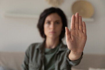 Fototapeta I said stop it. Blurred portrait of young lady looking at camera extending hand forward saying no enough to abuse family violence abortion. Focus on female palm close up raised in prohibiting gesture obraz